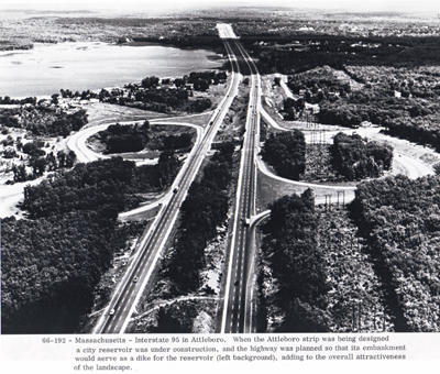 Massachusetts - Interstate 95 in Attleboro.  When the Attleboro strip was being designed, a city reservoir was under construction, and the highway was planned so that its embankment would serve as a dike for the reservoir (left background), adding to the overall attractiveness of the landscape.