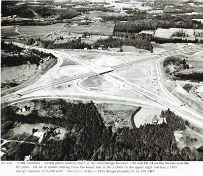 North Carolina - Aerial photo looking north at the interchange between I-26 and U.S. 64 on the Hendersonville by-pass. U.S. 64 is shown running from the lower left of the picture to the upper right and has a 1975 design capacity of 9,000 ADT.  Interstate 26 has a 1975 design capacity of 15,400 ADT.
