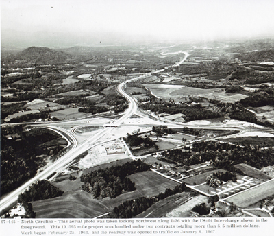 North Carolina - This aerial photo was taken looking northwest along I-26 with the U.S. 64 interchange shown in the foreground.  This project was handled under two contracts totaling more than $5.5 million.  Work began February 25, 1963, and the roadway was opened to traffic on January 9, 1967.