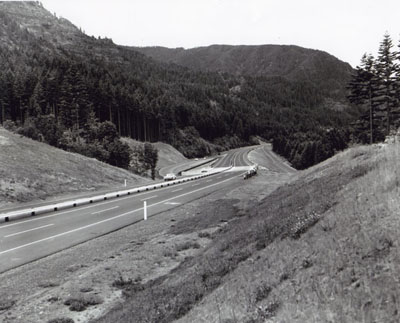 Interstate Route I-84 travels rough country along the Columbia River near Cascade Locks, Oregon. A narrow median with safety guard rail was used, since a broad median would have been too costly.