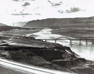 Interstate Route 90 slopes down from the foreground to cross an impressive structure over the Columbia River near Vantage, Wash.  The old bridge at this location was removed, since it would have been submerged after completion of Wanapum Dam downstream. The public utility district which built the dam contributed $4 million toward the new bridge.