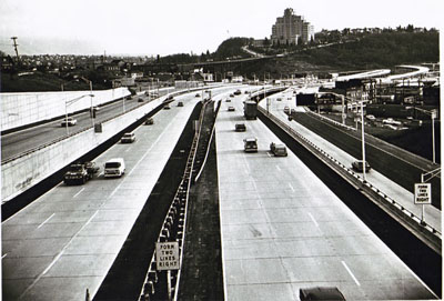 Washington - Seattle- area motorist lost little time in getting acquainted with the Seattle Freeway.  This photo, taken shortly after the ribbon-cutting ceremony, shows the prompt changeover of traffic to the new and safer highway.  The view is toward the south from the Yesler Way under-crossing bridge.
