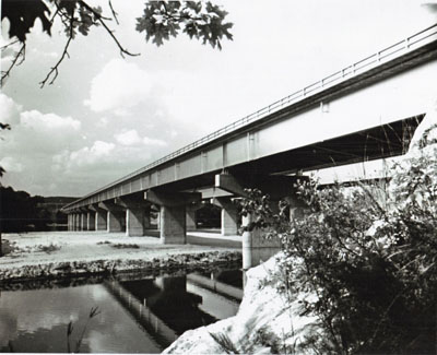 These to pairs of twin bridges on Interstate Route 90 in Wisconsin Illustrate both the functional grace and the diversity of design with which bridge builders fit structures to location needs.  The girder bridges supported on piers cross the Wisconsin River; the steel arches span Mirror Lake near the Wisconsin Dells. These bridges are part of a 55-mile, $32 million section of Interstate 90 between Madison and the Dells, opened to traffic in October 1961.