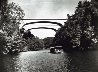 These tow pairs of twin bridges on Interstate Route 90 in Wisconsin Illustrate both the functional grace and the diversity of design with which bridge builders fit structures to location needs.  The girder bridges supported on piers cross the Wisconsin River; the steel arches span Mirror Lake near the Wisconsin Dells.  These bridges are part of a 55-mile, $32 million section of Interstate 90 between Madison and the Dells, opened to traffic in October 1961.