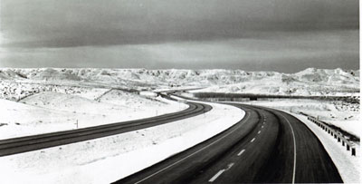 Interstate Route 90 traverses the snow-clad hill of northern Wyoming between Buffalo and Gillette.