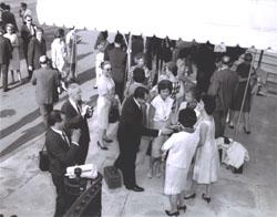 Mrs. Rex Whitton, wife of the Federal Highway Administrator, looks on (in sunglasses) as Deputy Federal Highway Administrator Laurence Jones greets Cabinet wives before the Landscape-Landmark Tour.  Next to him is Mrs. Mary Connor (facing camera, wearing necklace with disc to waist), wife of Secretary of Commerce John T. Connor.