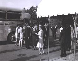 President Lyndon Johnson looks on (right) as participants in the Landscape-Landmark Tour enter chartered tour bus.
