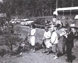 Along I-95 in Virginia, Federal Highway Administrator narrates as Lady Bird Johnson (left) shades her eyes after taking a turn with the shovel to fill in the hole around a dogwood tree planted for the occasion in cooperation with the Associated Clubs of Virginia for Roadside Development.  Muriel Humphrey, wife of Vice President Hubert H. Humphrey, is next to Whitton.  Third woman is unidentified.