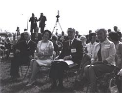 Photographers records events as Federal Highway Administrator opens his notes while listening to Douglas B. Fugate, Chairman and Commissioner of the Virginia Department of Highways, with (left to right) Virginia Governor Albertis Harrison, Lady Bird Johnson, and Muriel Humphrey.