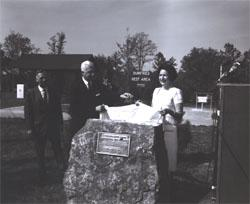 Lady Bird Johnson and Governor Albertis Harrison unveil a plaque at dedication of the I-95 Dumfries Wayside Shelter in Virginia.  Looking on is Douglas B. Fugate, Chairman and Commissioner of the Virginia Department of Highways.