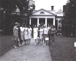 Posing before Monticello, home of Thomas Jefferson.  Identified participants are Mary Connor (third from left), wife of Secretary of Commerce John T. Connor; Lady Bird Johnson (center), still holding her color camera; Trudye Fowler, wife of Secretary of the Treasury Henry T. Fowler; and Muriel Humphrey (third from right), wife of Vice President Hubert H. Humphrey.