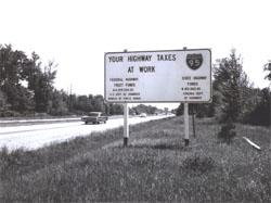 """YOUR HIGHWAY TAXES AT WORK"" sign along I-95 in northern Virginia.  I-95 to Richmond had been completed in October 1964."