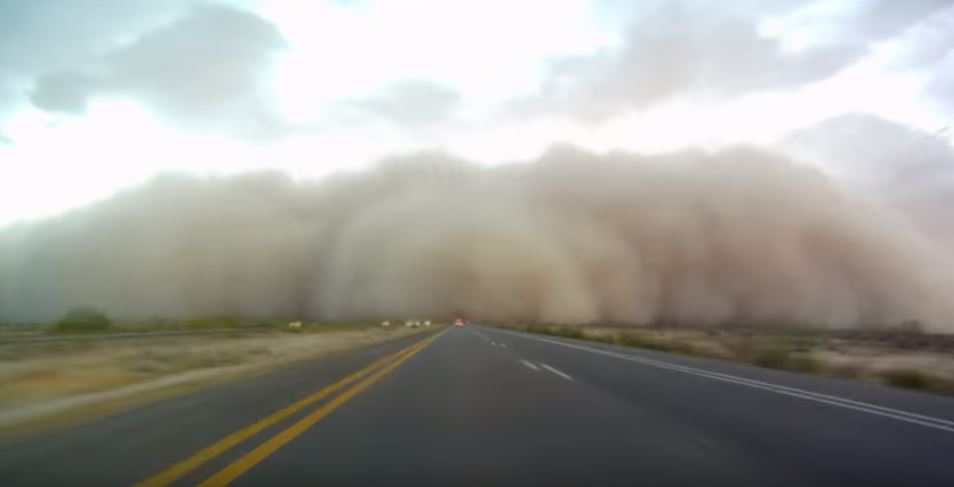 A huge dust storm streches across a road