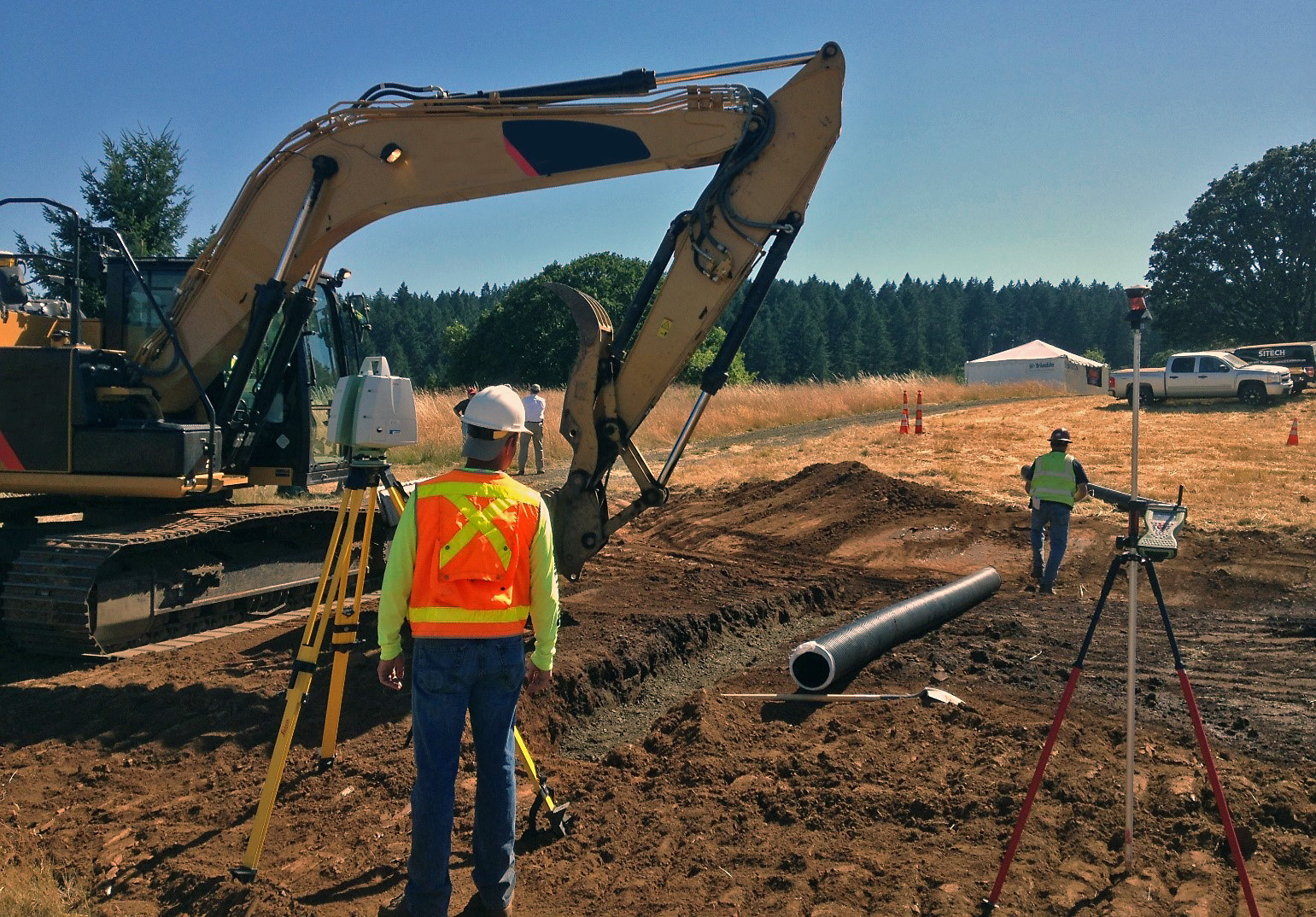 Worker in orange safety vest and hardhat stands near survey equipment and an excavator during pipe installation.