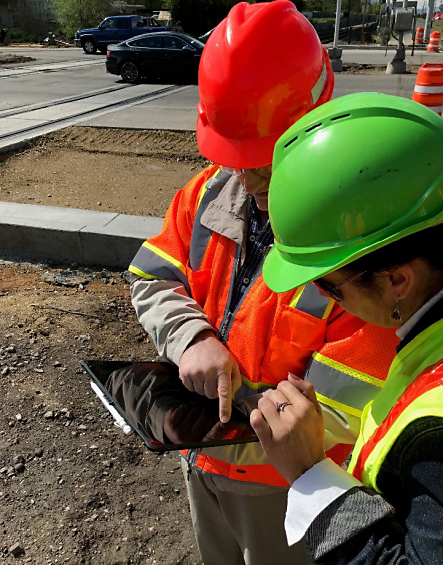Man and woman wearing orange and yellow safety vests and hardhats standing at a construction site referring to information on a mobile tablet.