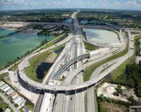 Photo. Overhead daytime view of a highway with an interchange crossing over it. Copyright, Smith Aerial Photos