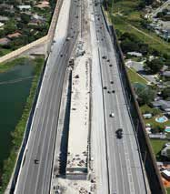 Photo. Overhead daytime view of traffic on an eight-lane highway.