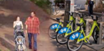 Photo of couple walking baby and bike-share bikes parked in rack.