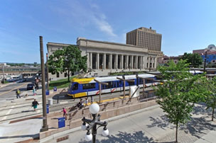 Image shows light rail with people crossing the streets and Union Depot building in background.