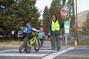 Crossing guard holds STOP sign as children walk across the streets, one walking a bicycle.