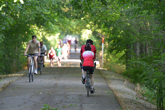 People walking and biking along the tree-lined Monon Trail.