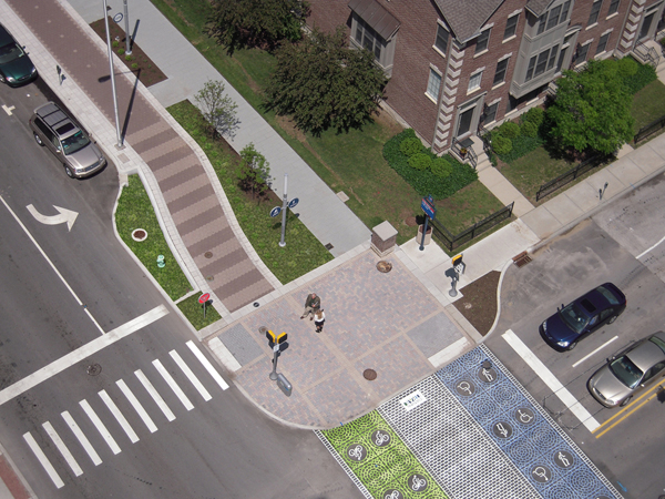 Aerial view of an intersection showing an extended curb and special pavement markings indicating the lanes for each trail as it crosses the street. The bike lane is painted in a green pattern and repeated images of a person riding a bike. The pedestrian lane is painted in a blue pattern with repeated images of both a pedestrian and a wheelchair.