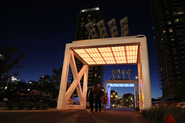 Night image of two bridge art structures, each glowing with LED lights.