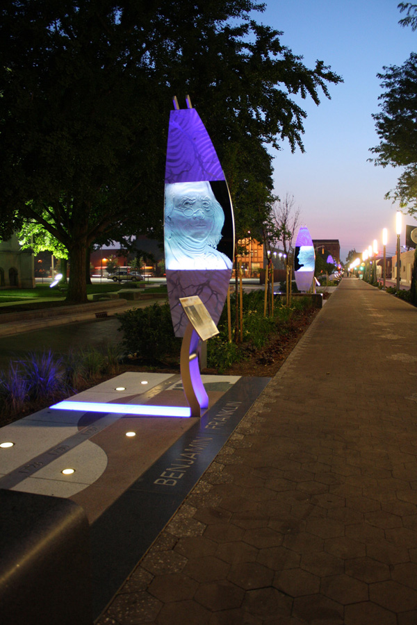 The trail at night with art structures lit in purple. The foreground structure depicts an image of Benjamin Franklin.