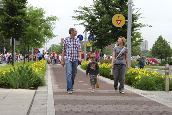 A man, woman, and small child walking along the Cultural Trail. In the background a large group of people can be seen at an intersection along the trail.