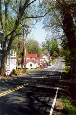 Country road running through rural Upperville. The street is lined with houses on the left and trees on the right.