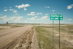 photo of gravel surfaced roads and a road sign; left to Buffalo Gap, Right to Red Shirt