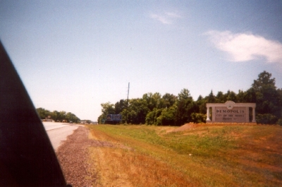 "photo of land beside road with Demopolis ""City of the People"" sign"