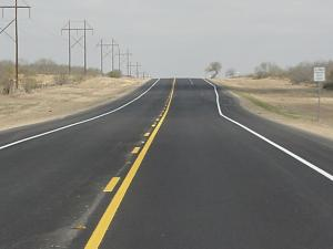 photo of a two lane undivided road with a right side pull over lane in the distance