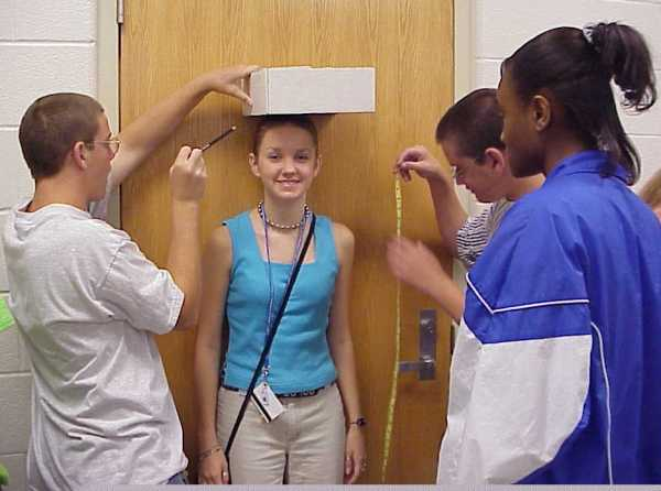 photo: Group of students in a classroom. One girl standing by a doorway while other students measure the girl's height.