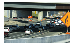This photo shows a busy freeway interchange that is currently under construction.   Traffic is heavily congested in both directions and there are signs indicating upcoming lane closures.