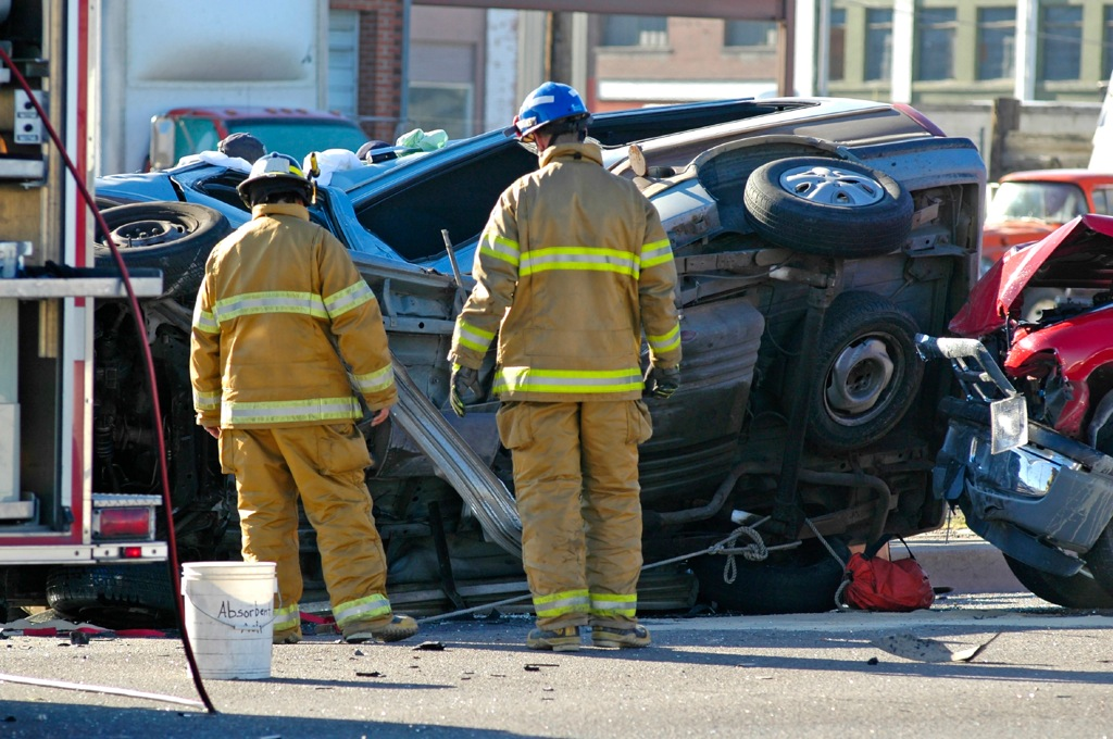 This photo shows a serious traffic crash where one car has crashed into another and one vehicle ends up on its side.  Two emergency response personnel are shown looking at the underside of the crashed car.