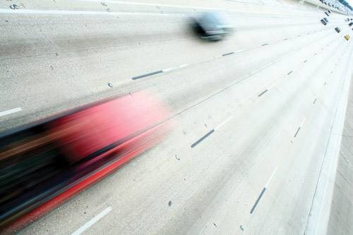 Photograph taken from an overpass showing two cars with motion blurs speeding by on a multi-lane highway below.